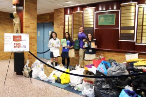 Students stand among the donations to this year's Dual-Coat/Food Drive.