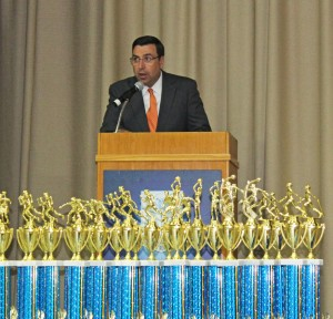 Athletic Director Mike McCleary speaks at Athletic Awards Night. In the foreground are the many trophies to present.